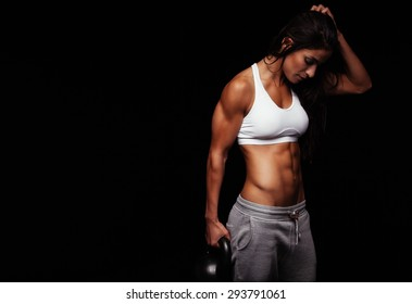 1b72f4aad9 Fitness woman exercising crossfit holding kettle bell. Fitness instructor on  black background. Female model