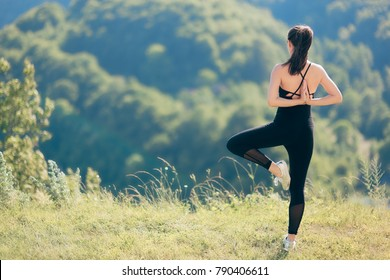 Fitness Woman Exercising Flexibility and Balance in Beautiful Nature. Girl reaching arms behind in tree pose admiring natural landscape