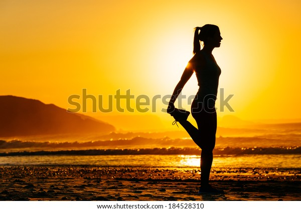Fitness woman exercising and stretching legs on beautiful summer sunset or morning at beach. Female runner warming up or cool down.