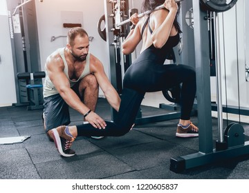 Fitness woman exercising with fitness trainer in gym. Personal fitness instructor. Personal training.