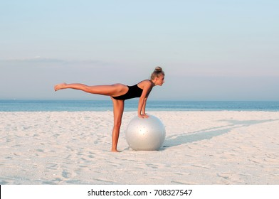 Fitness woman with fit ball on beach outdoors. Fitness girl in one-piece swimsuit work out with pilates ball at seaside
