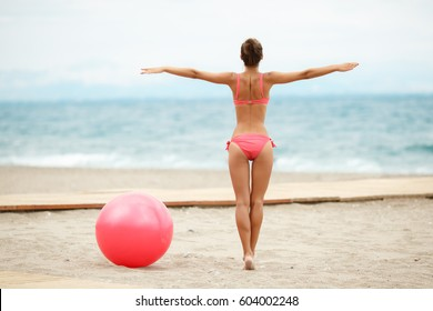 Fitness woman with fit ball at tropical beach outdoors. Fitness girl in bikini work out with pilates ball at beach. Female sport instructor hold yoga exercise ball outdoor in morning - yoga worout