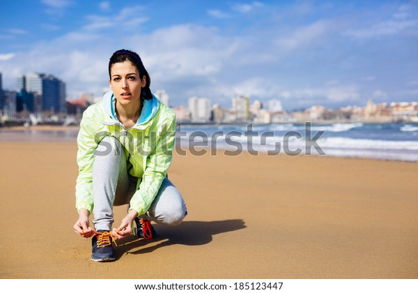 Fitness woman getting ready for running challenge at city beach in Gijon, Asturias, Spain. Female runner lacing sport shoes before training.