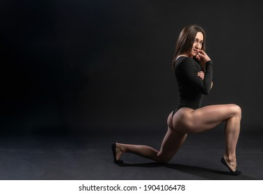 fitness woman gym black. In a black bathing suit. Beautiful, human leg posture. figure, torso, waist. Waist belly, the squat is performed