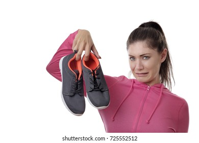 fitness woman holding up her smelly exercise shoes