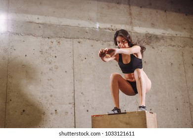 Fitness woman jumping on box training at the gym, fit exercis