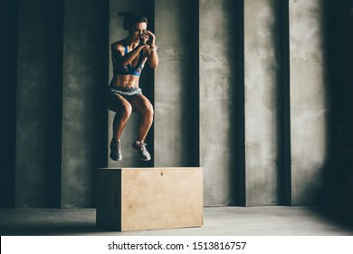 Fitness woman jumping on box while training at the gym,girl doing cross fit exercise. Sports concept, and healthy lifestyle.