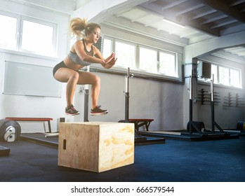 Fitness woman jumping on box training at the gym, cross fit exercise