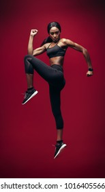 Fitness woman jumping over red background. Full length of healthy young african woman exercising and jumping in studio.