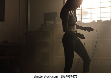 Fitness woman with jumping rope in gym. Female exercising with skipping rope at health club.