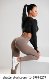Fitness woman in leggings on gray background. Athletic girl with beautiful butt