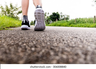 fitness woman legs running at forest trail