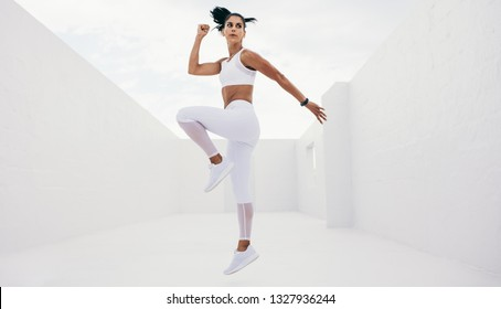 Fitness woman lifting one leg while jogging in place. Woman in fitness wear doing workout.