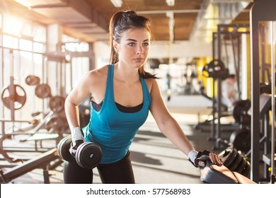 Fitness woman lifting weights in gym.