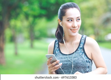 Fitness woman is listening to music from her mobile phone while running in the park.And she was smiling happily.