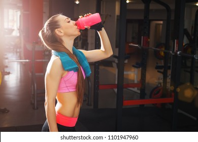 Fitness woman with long blonde hair in pink top and shorts with blue towel drinking water while resting in gym