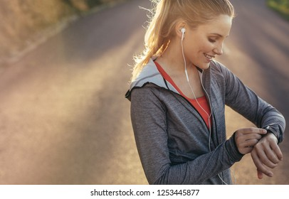 Fitness woman looking at her wrist watch during her morning fitness run. Smiling female athlete checking time standing on road while listening to music on earphones.