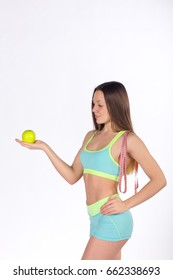 Fitness woman looks at apple, measuring tape on the shoulder, white background, side view. Vitamin care, health food. Healthy lifestyle