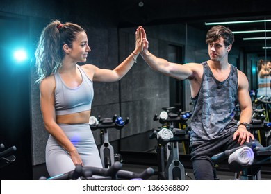 Fitness woman and man giving each other a high five after cycling training in gym. Fit couple high five after workout in health club.