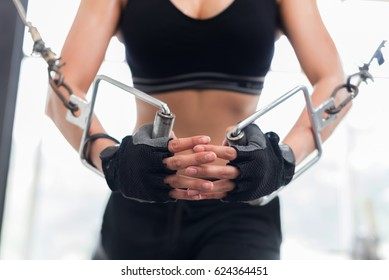Fitness woman with muscular and tanned body crossover in the gym; Fitness - concept of healthy lifestyle.