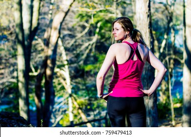 Fitness woman in nature trail looking over shoulder. Fitness lifestyle concept.