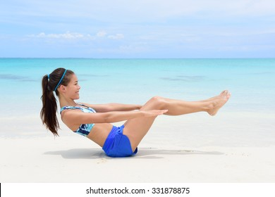 Fitness woman on beach with toned in shape body body doing v-up crunch ab toning exercise workout as part of an active lifestyle for weight loss.