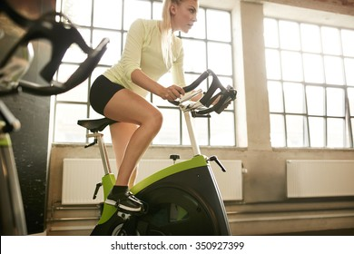 Fitness woman on bicycle doing spinning at gym. Fit young female working out on gym bike.