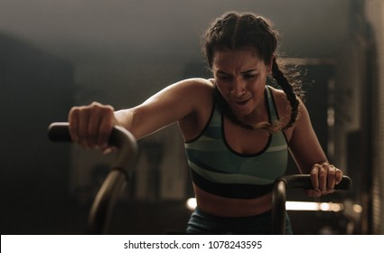 Fitness woman on gym bicycle doing exercise. Female putting full effort while exercising on gym air bike.