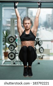 Fitness Woman Performing Hanging Leg Raises Exercise - One Of The Most Effective Ab Exercises