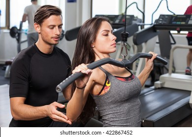 Fitness woman with personal trainer at gym