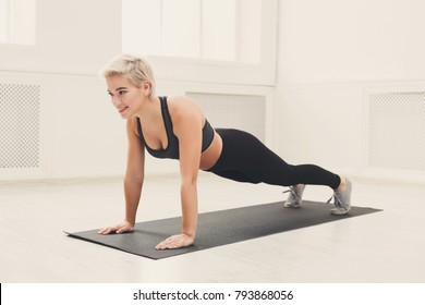 Fitness woman plank workout training at white background indoors. Young slim girl makes exercise. Healthy lifestyle, gymnastics concept