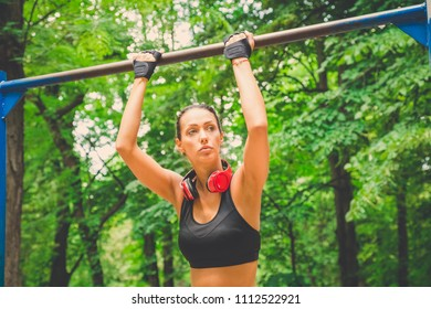 Fitness woman preparing for doing pullups in nature. Healthy lifestyle concept.