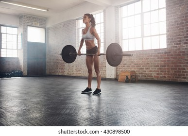 Fitness woman preparing to practice deadlift with heavy weights in gym. Female doing heavy weight lifting work out in health club.