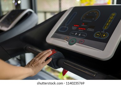 Fitness woman Push the emergency button on the treadmill. Concept of healthy lifestyle in the gym.
