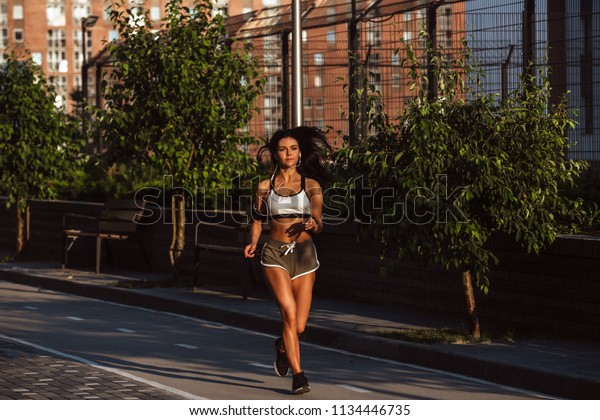 Fitness woman runner relaxing after city running and working out outdoors.