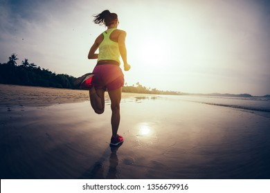 Fitness woman runner running on sunrise beach