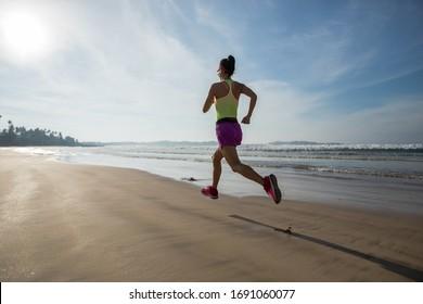 Fitness woman runner running on sunrise beach