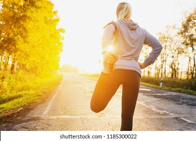 Fitness woman runner stretching legs before run on the road