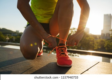 Fitness woman runner tying shoelace before running