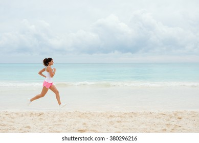 Fitness woman running at the beach on summer vacation. Healthy female athlete training outdoor.