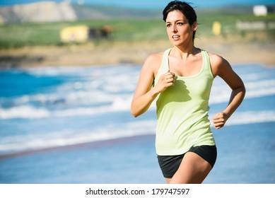Fitness woman running fast on beach.