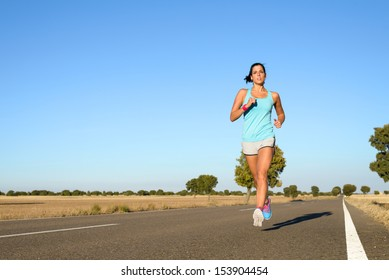 Fitness woman running fast in rural straight road. Runner exercising and training hard for marathon. Full body sport scene with copy space.