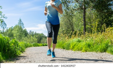 Fitness woman running at forest trail A woman with an athletic pair of legs going for a jog or run on forest trail. Healthy lifestyle concept. Female runner jogging down an outdoor trail on sunny day.