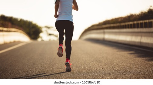 Fitness woman running on city road