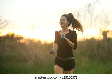 fitness woman running outdoors.  female jogging in morning with bright sunlight.