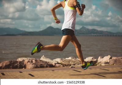 Fitness woman running training for marathon on sunny coast trail