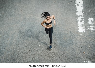 Fitness woman she is running the road. Top view