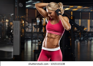 Fitness woman showing abs and flat belly. Muscular girl, shaped abdominal