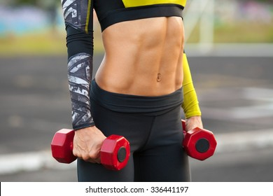 Fitness woman showing abs and flat belly. Muscular girl with dumbbels, shaped abdominal, slim waist