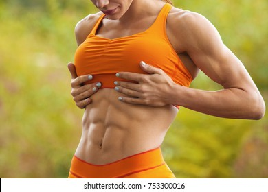 Fitness woman showing abs and flat belly. Athletic girl outdoors, shaped abdominal, slim waist